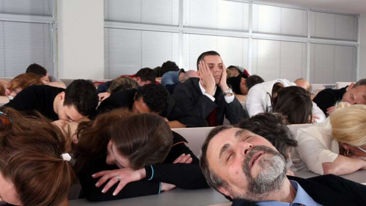 People sleeping during a business presentation, only one is still awake