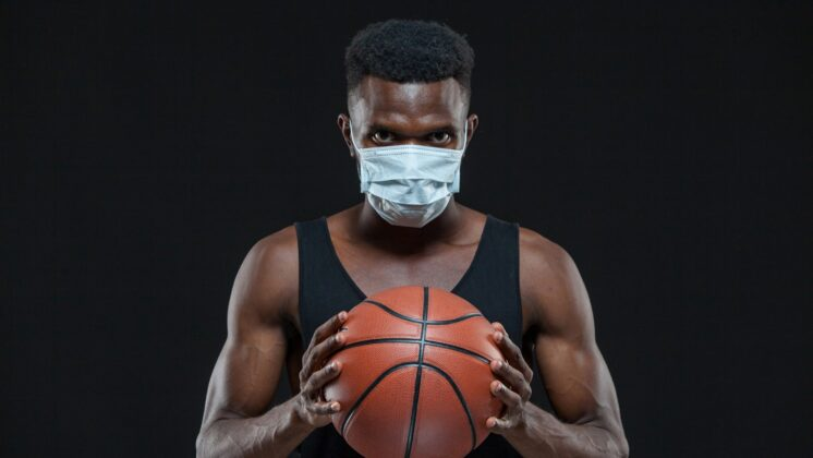 Black male basketball player in protective mask is holding a ball, preventing the spread of coronavirus infection