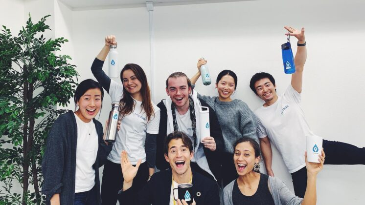 The mymizu team, posing with reusable water bottles that help reduce plastic waste