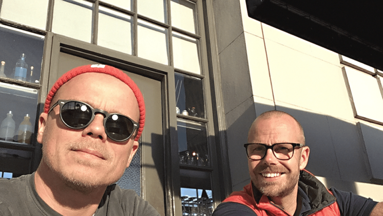 Friends and Pickit cofounders Henrik Bergqvist and Mathias Bjorkholm sit together outside on a sunny day