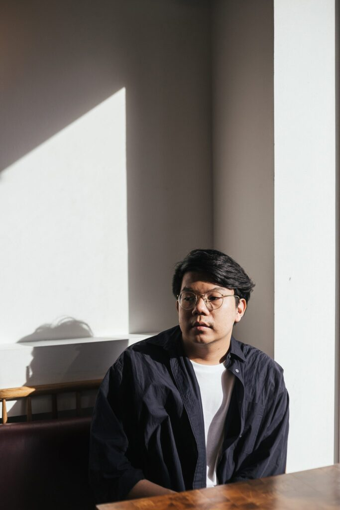 Nakrob Moonmanas, a Thai gentleman dressed in an black shirt and white t-shirt, sits in the sun.