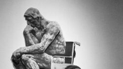 Thinker, a famous sculpture by Rodin, has be photoshopped into a wheelchair.