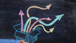 Man holding an open box with colorful arrows pointing out the top, drawn on blackboard