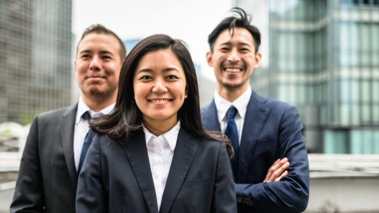 A woman stands in front of two men. All three face the camera, smile, and are wearing business attire.