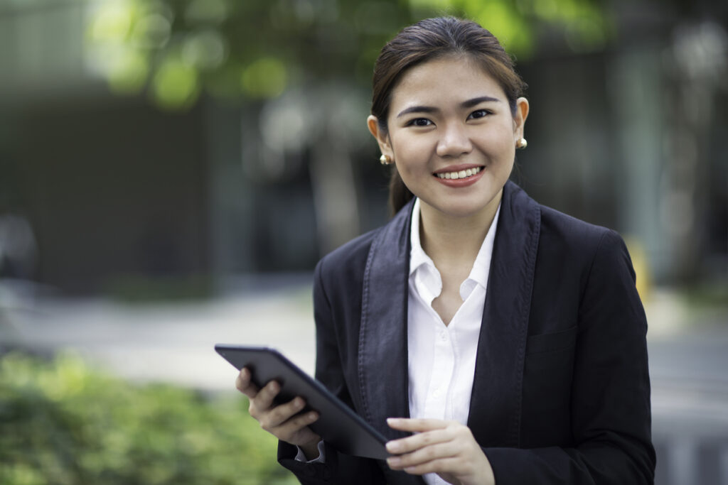 Filipina businesswoman holding a tablet and looking into the camera.