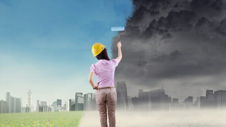 Woman paints a green city over a grew polluted one.