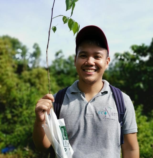 Joshua Caampued holding a tree sapling in a plastic-alternative EcoNest bag at a community activity