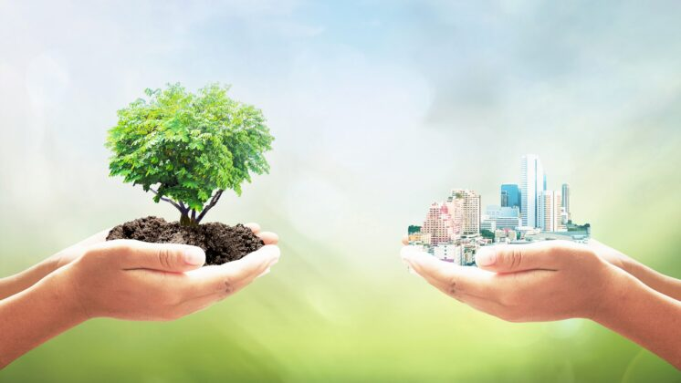 Two human hands, one holding a tree, the other a big city over blurred nature background, representing SDGs