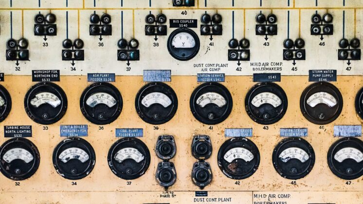 Panel of analog meters, dials, and switches in an abandoned power station.