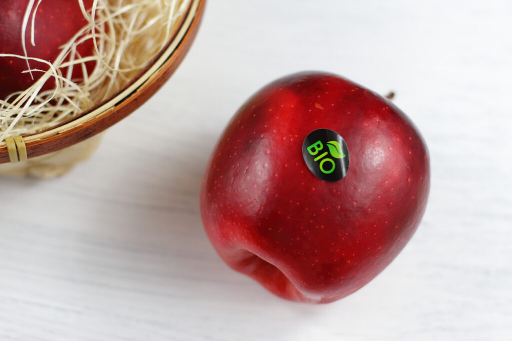 A red apple with a sticker on it sitting on a table.