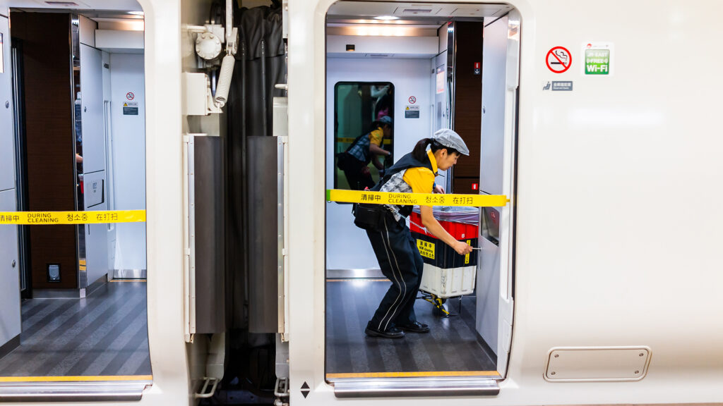Japanese Shinkansen cleaner performing the seven-minute miracle inside the train at an airport terminal station with equipment