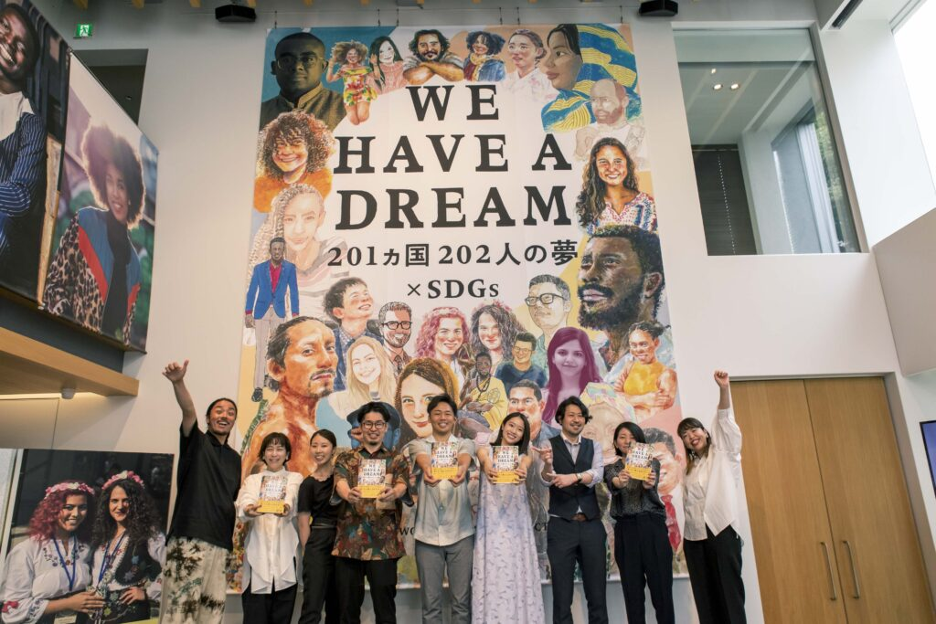 An image of the launch party for WE HAVE A DREAM with the publishing team standing before a large banner of the book cover