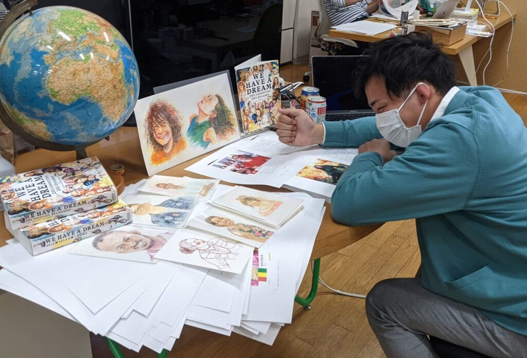 Ichikawa sits hunched over a table of sketches and drafts for WE HAVE A DREAM