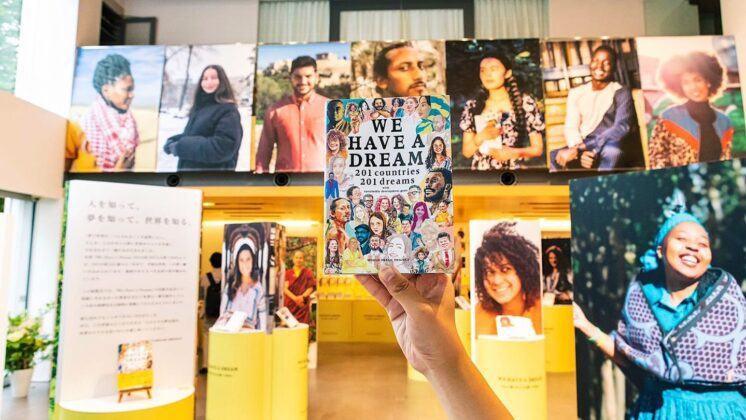 A hand holds up the book WE HAVE A DREAM with enlarged portraits of some of the global contributors in the background