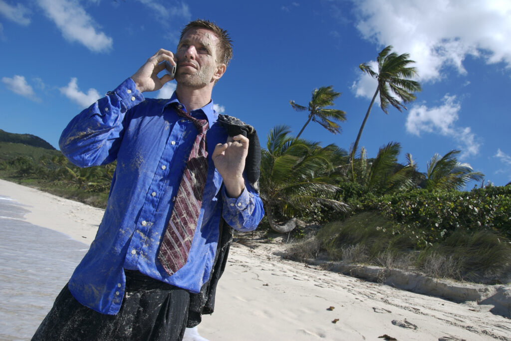 Businessman in disheveled clothing tries to find cell reception on a desert island