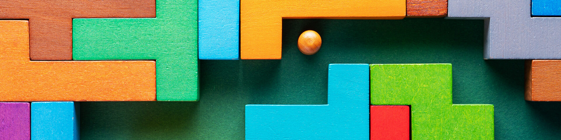 A wooden ball rolls through a labyrinth of colorful wooden blocks like critical thinking guiding decisions against cognitive bias