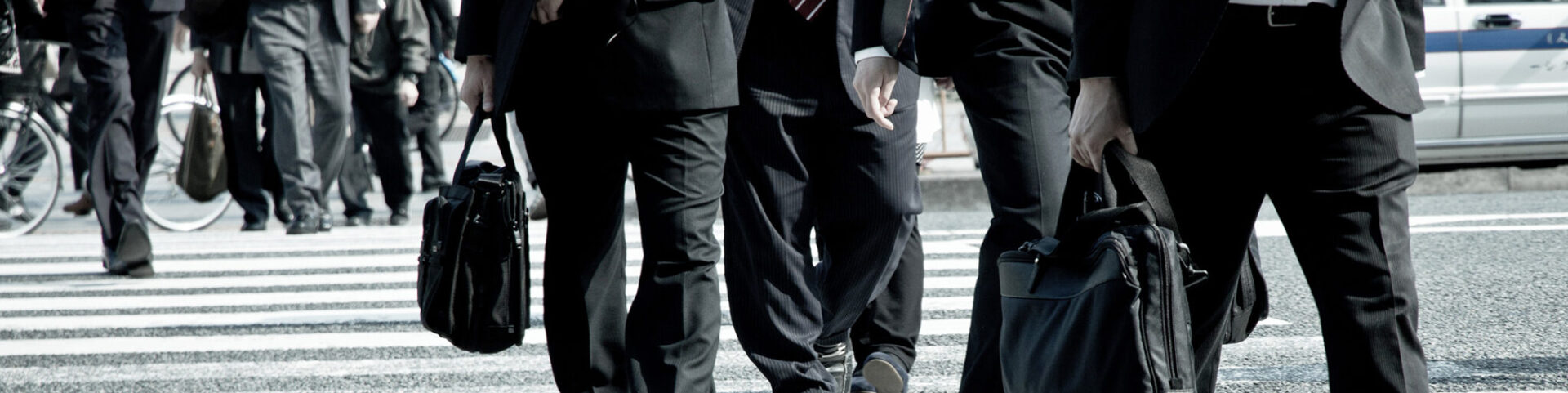 Office workers crossing a street on their way to the office, following the uniform Japanese working culture