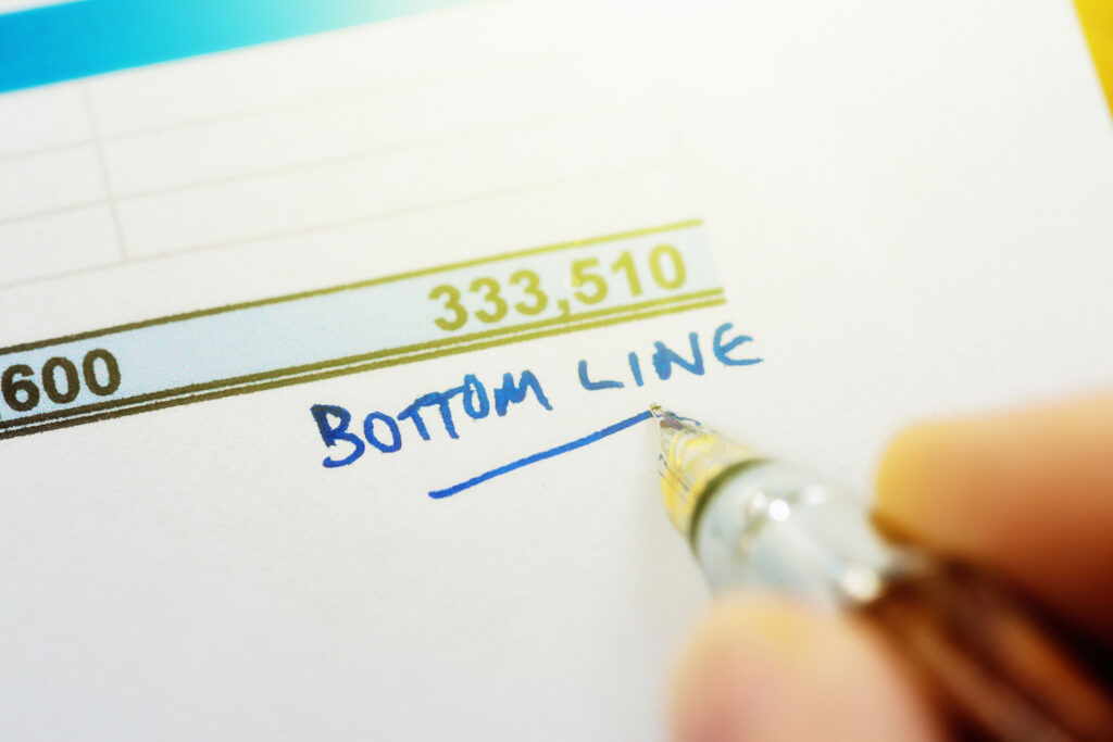 """The bottom of a financial sheet with a large number in green, under which a hand is writing and underlining the words """"bottom line"""""""