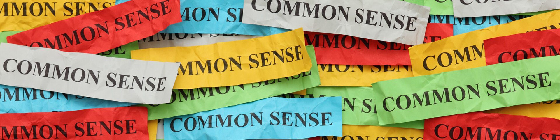 """Many-colored strips of paper overlaid and all reading """"common sense"""""""