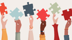 A row of multiracial women's hands lift up puzzle pieces to show the importance of thinking through a DEI business strategy