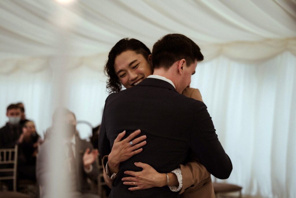 Kan and his husband Tom happily embracing at their wedding