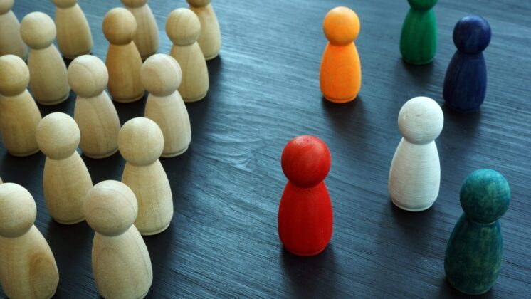 Unpainted pawns stand in strict rows facing colorful, dispersed pawns on a table, representing a workforce failing to integrate true DEI